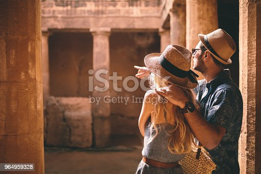 Young tourists couple on summer holidays visiting ancient archaeological site with stone columns in Egypt