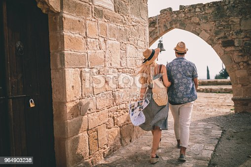 Tourists couple on summer holidays visiting ancient stonebuilt archaeological church with arches in Italy