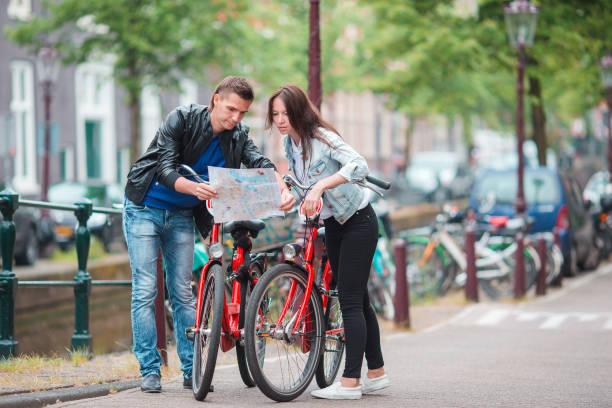 junge touristen-paar auf der suche auf karte in europäischen städten. familie mit zwei im urlaub in amsterdam - hochzeitsreise amsterdam stock-fotos und bilder