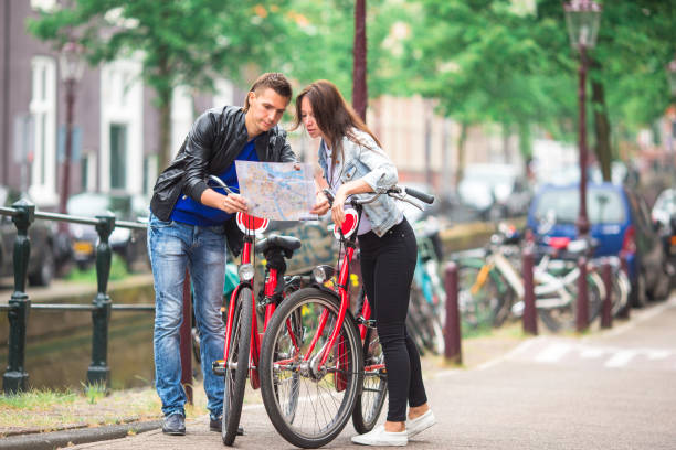 junge touristen-paar auf der suche auf karte in europäischen städten. - hochzeitsreise amsterdam stock-fotos und bilder