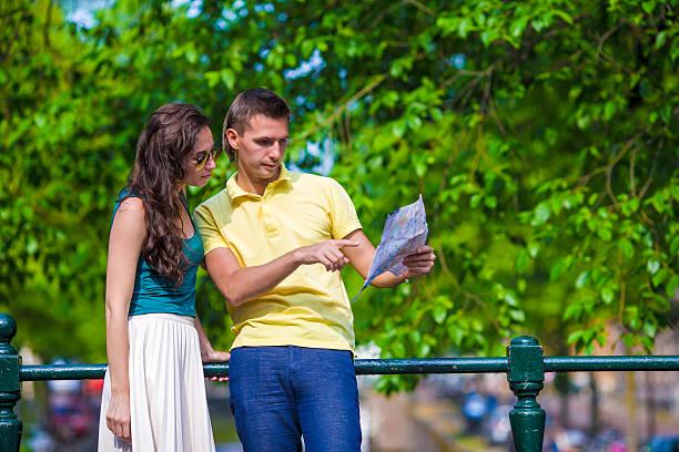 junge touristen paar blick auf karte in europäischen stadt - hochzeitsreise amsterdam stock-fotos und bilder