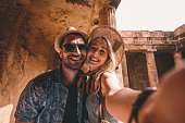 Smiling tourists on summer vacations in Greece taking selfies at ancient landmark with stone columns
