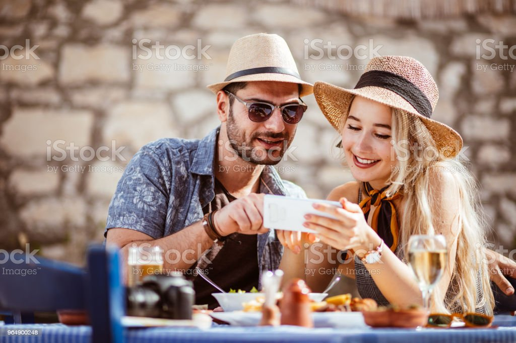 Young tourists couple using smartphone at traditional Greek restaurant royalty-free stock photo