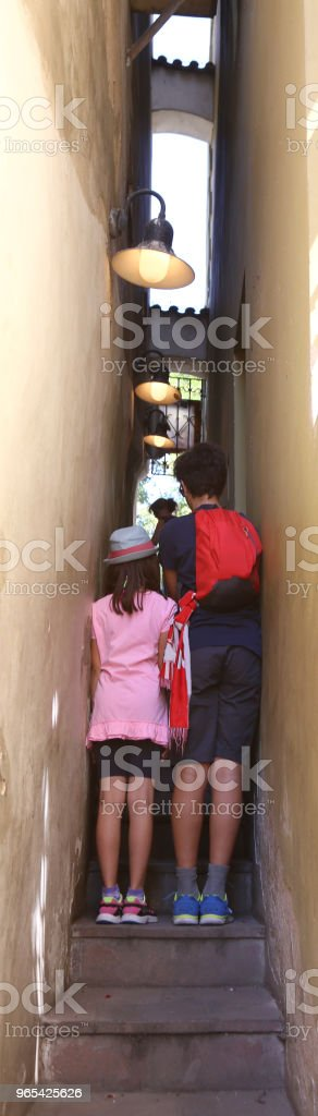 Young tourists in the narrowest street in the world in the city zbiór zdjęć royalty-free