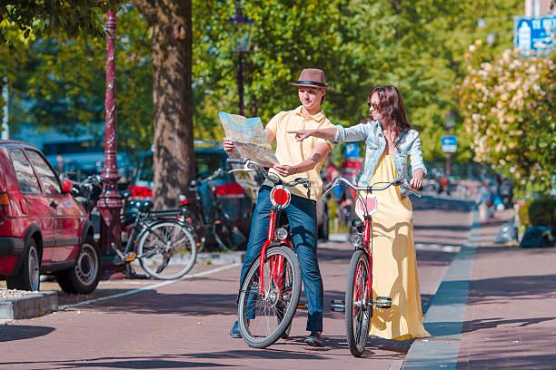 junge touristen schaut an karte mit fahrräder in europäischen stadt - hochzeitsreise amsterdam stock-fotos und bilder