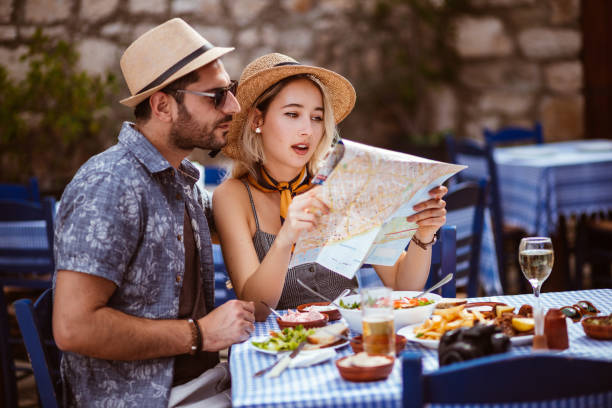 Young tourists on vacations reading map at traditional Greek restaurant stock photo