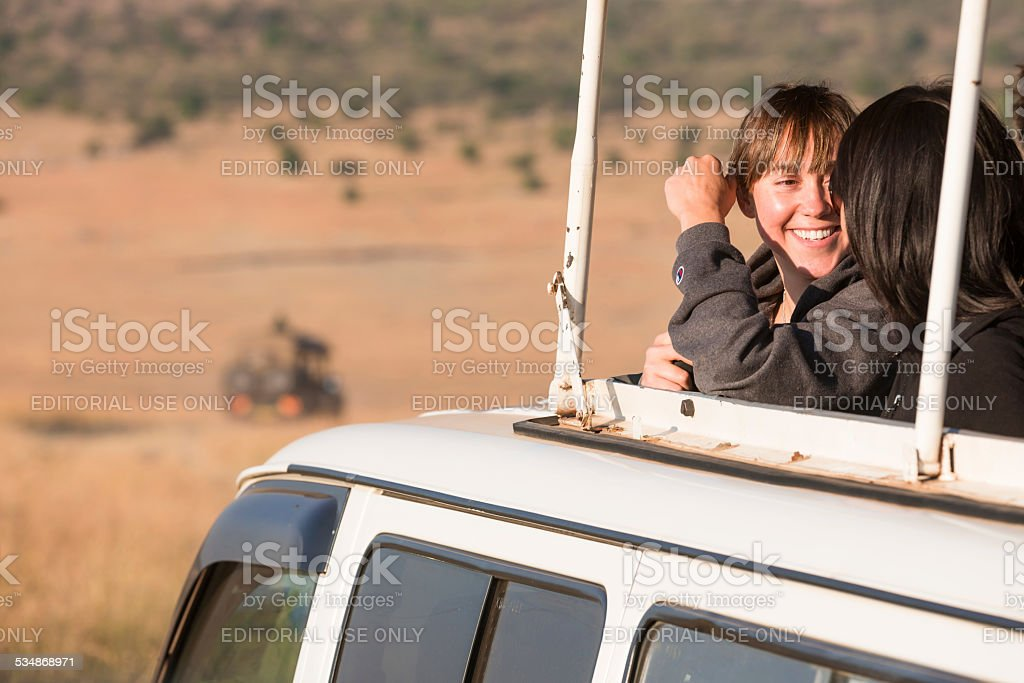 Young tourist girls in off-road vehicle, tracks and safari cars and...