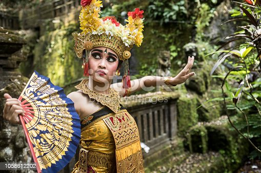 A young teenage Balinese girl wearing a traditional Barong costume gracefully poses with a hand fan and dances in a Hindu temple. The Hindu culture is still well preserved and children learn at a very young age the art of Ramayana and dance.