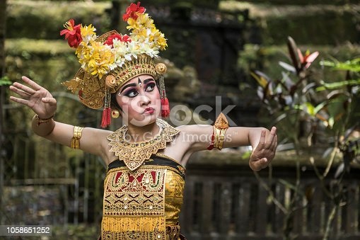 A young teenage Balinese girl wearing a traditional Barong costume gracefully poses and dances in a Hindu temple. The Hindu culture is still well preserved and children learn at a very young age the art of Ramayana and dance.