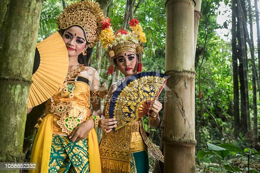 In a natural bamboo forest environment, two young teenage Balinese girls wearing a traditional Barong costume and holding a hand fan gracefully poses in front of the camera. The Hindu culture is still well preserved and children learn at a very young age the art of Ramayana and dance.