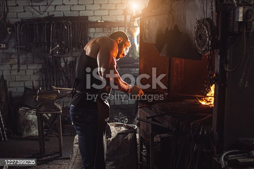 istock young traditional caucasian blacksmith working with open fire in workshop 1227399235