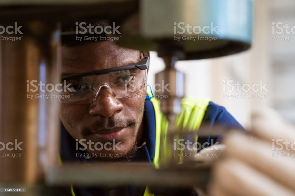 Young trainee using yoke machine at factory Close-up of young trainee using yoke machine. Male engineer is wearing protective glasses in factory. He is working in industry. 25-29 Years Stock Photo