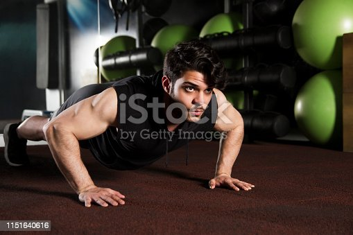 Young handsome man with muscular build doing push-ups on gym floor