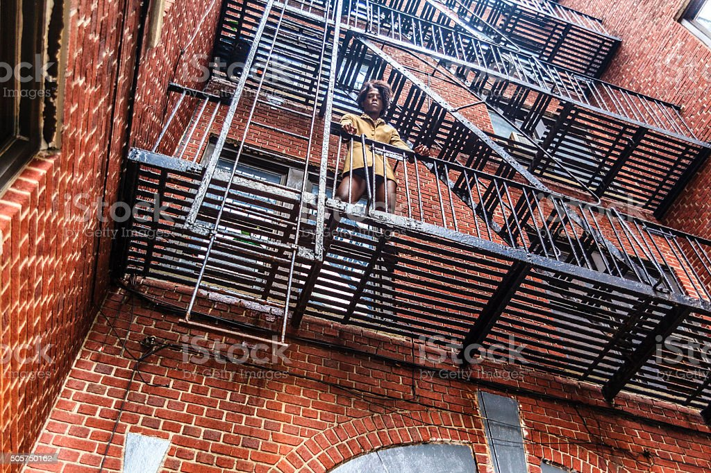 Young transgender woman on the fire stair stock photo