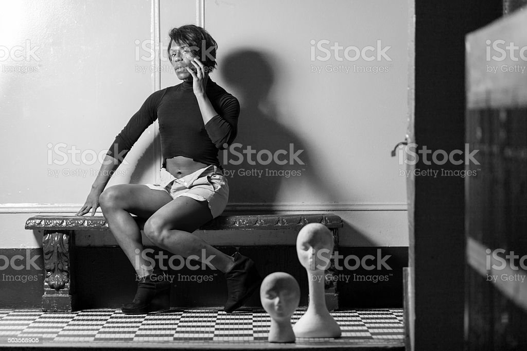 Young transgender woman posing with dummyes stock photo