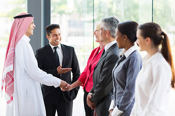 young translator introducing arabian businessman - translator stock photos and pictures
