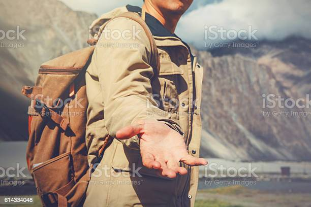 Photo of Young travel man lending a helping hand in mountain