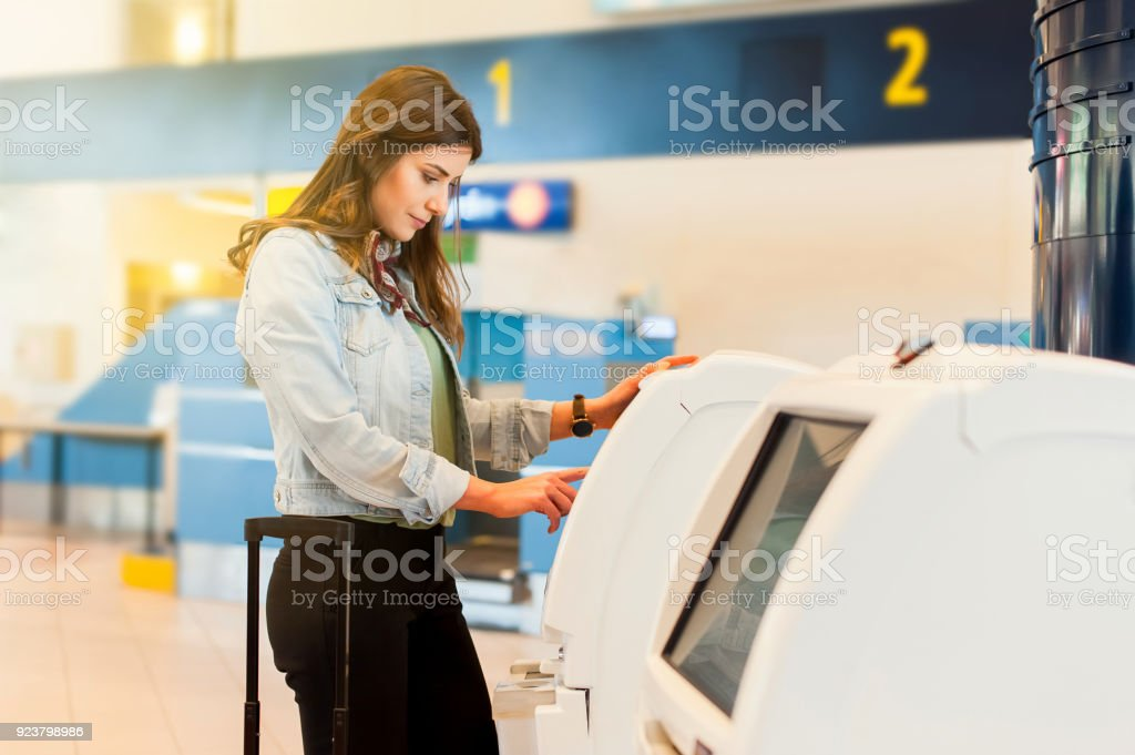 Young travel woman in the airport using atm machine stock photo