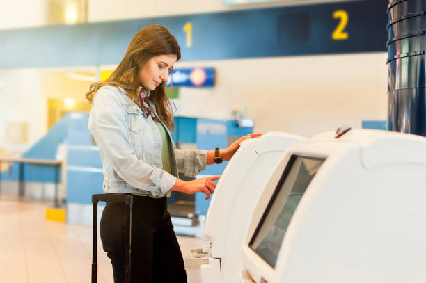 young travel woman in the airport using atm machine - airport check in counter stock pictures, royalty-free photos & images