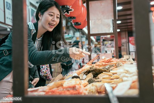 Japan travel lady pointing at the seafood on the mobile kitchen. girl tourist experience japanese culture. young traveler hungrily buying street food.