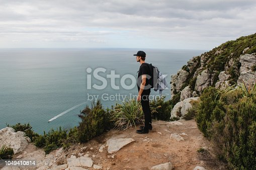 Young male traveler is standing on a cliff ledge looking out to the pacific ocean in New Zealand.