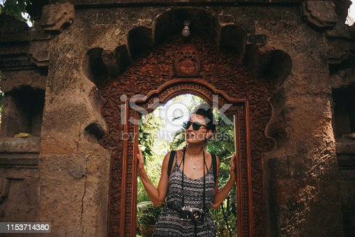Young woman, solo tourist, walking through the old Hindu temples in Ubud, on the island of Bali, Indonesia.