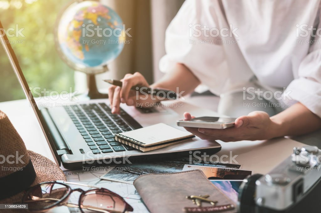 Young traveler planning vacation trip and searching information or booking hotel on laptop, Travel concept Young traveler planning vacation trip and searching information or booking hotel on laptop, Travel concept Bag Stock Photo