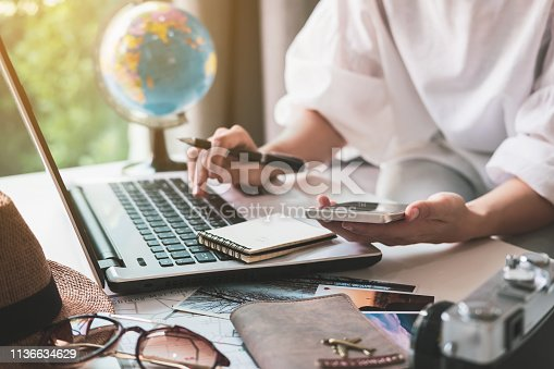Young traveler planning vacation trip and searching information or booking hotel on laptop, Travel concept