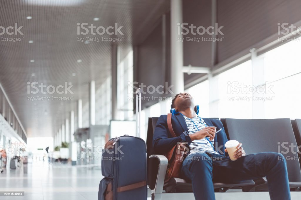 Young traveler sleeping at airport waiting area stock photo