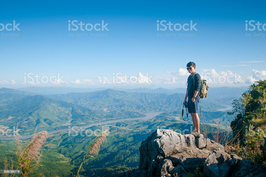 Young traveler standing on the mountains looks into the sunset. stock photo