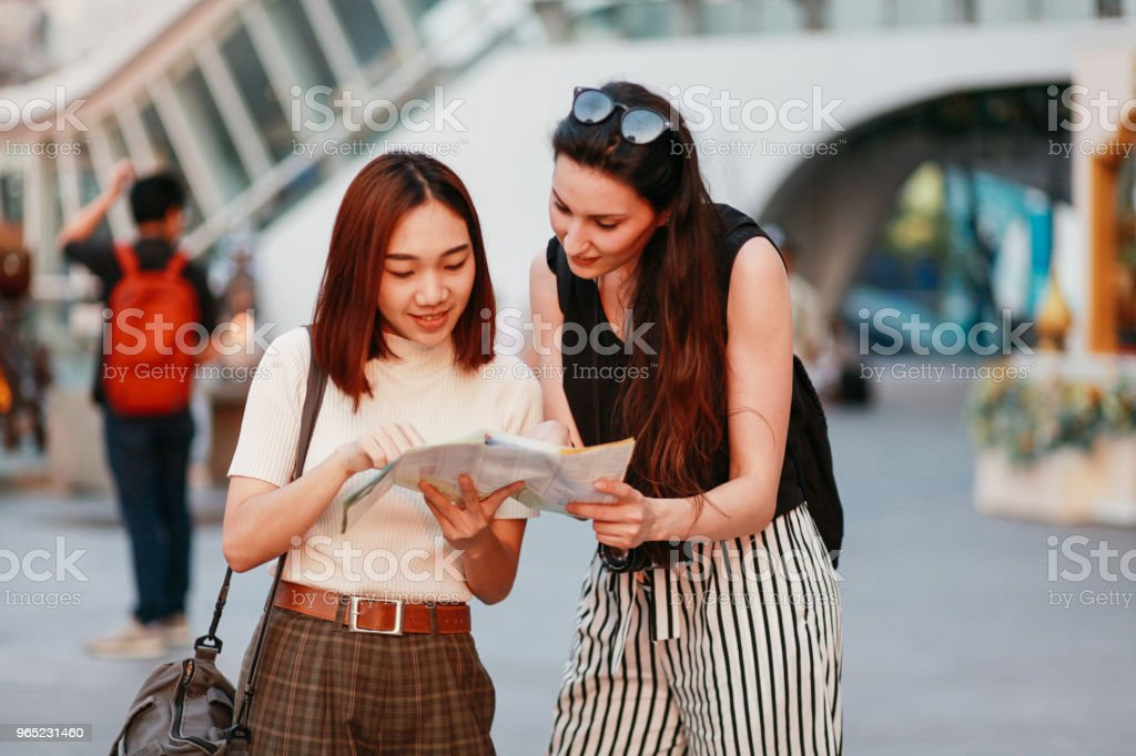 Young traveler woman asking a local about guidelines royalty-free stock photo