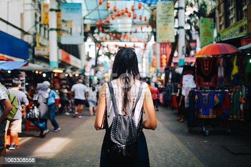 Young traveler woman walking through the stalls in Chinatown district of Kuala Lumpur, Malaysia.