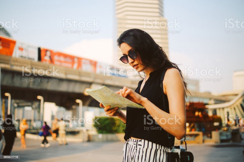 Young traveler woman looking at the map in Bangkok - Royalty-free Adult Stock Photo