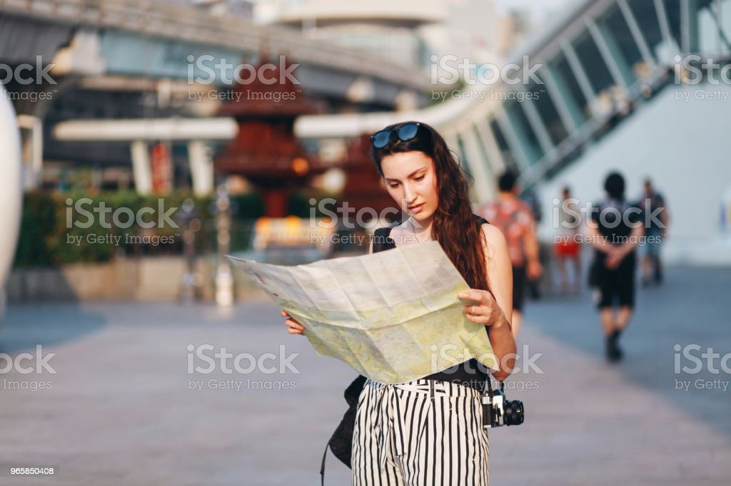 Young traveler woman looking at the map in Bangkok - Стоковые фото Азия роялти-фри