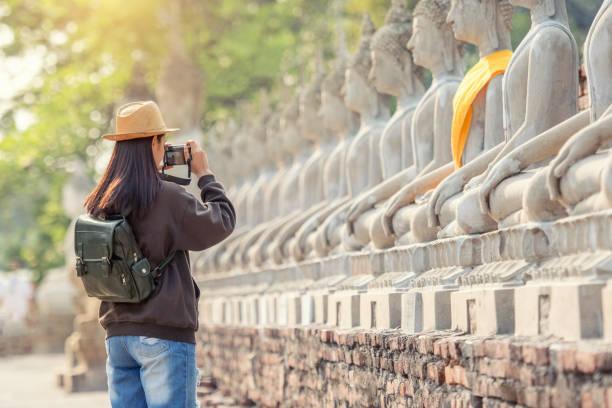 tourisme femme jeune voyageur en thaïlande prendre une photo état de bouddha dans le vieux temple vintage au cours de la période heureuse matin - camera sculpture photos et images de collection