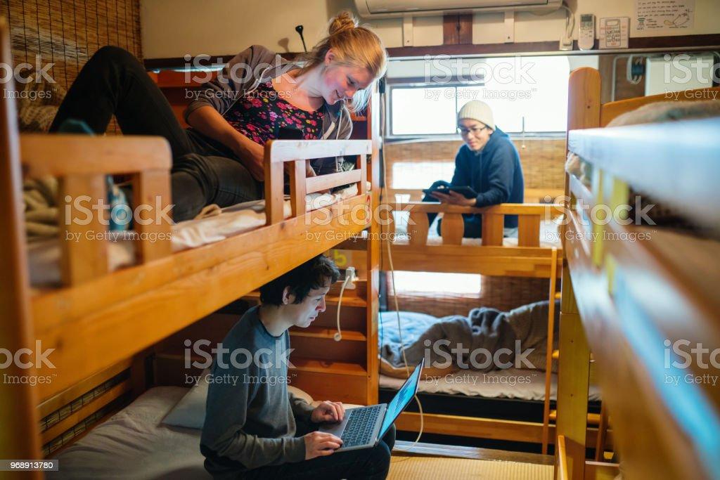 Jeunes voyageurs dans un dortoir de style Auberge de routards à l'aide d'un ordinateur portable - Photo