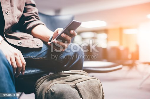 istock Young travelers living smartphones waiting for mass transit system waiting for the plane to go on vacation on weekend over blurred Terminal. select focus and Film Tone with Light fair 839040118