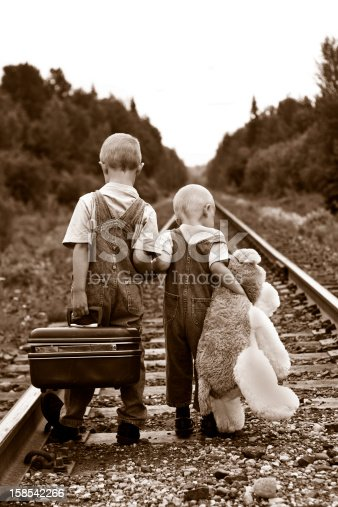 An old style photograph of brothers dressed in old fashioned clothing walking down railroad tracks.  The oldest is carrying a suitcase, and the youngest a large stuffed toy.