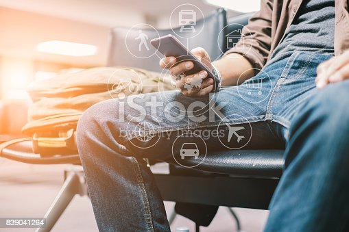 istock Young travelers Use a smartphone to find travel information from the application. waiting for mass transit system go vacation on weekend over blurred Terminal. select focus and Film Tone with Light fair 839041264