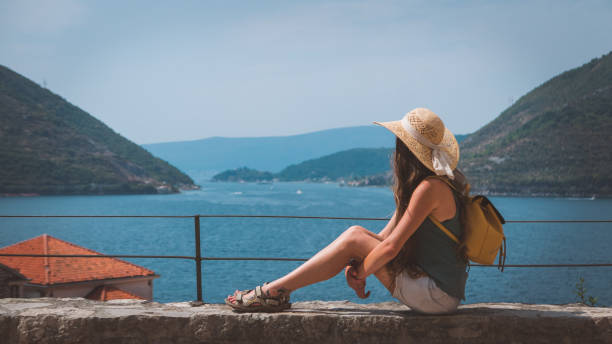 junge reisende frau in shorts zu betrachten und beobachten die bucht - salzwasser sandalen stock-fotos und bilder