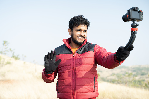 Young traveller busy talking with camera on top of Mountain - Concept of travel vlogger, blogger or influencer recording video during hiking