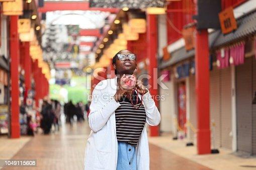 A young black woman exploring the markets and backstreets of Asakusa, Tokyo.