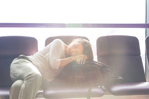 young traveller taking a nap while waiting her flight Young woman in a airport lounge with jet lag issues.  She's sleeping while waiting her delayed flight jet lag stock pictures, royalty-free photos & images