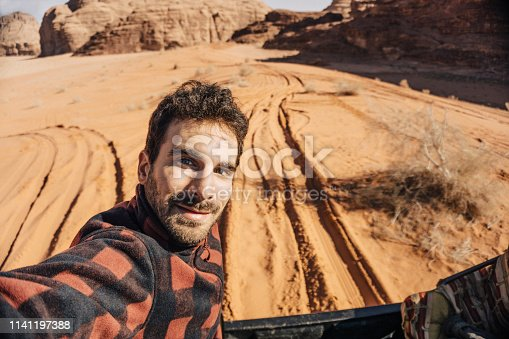 Young traveller taking a selfie in the desert of Wadi Rum, Jordan