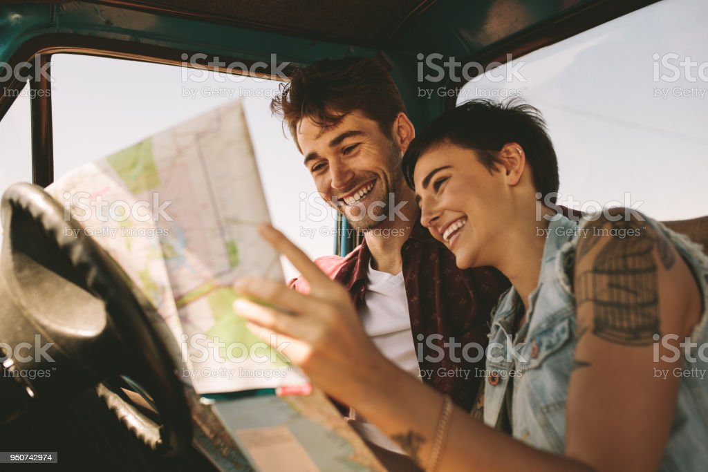 Young travellers on a road trip looking at map stock photo