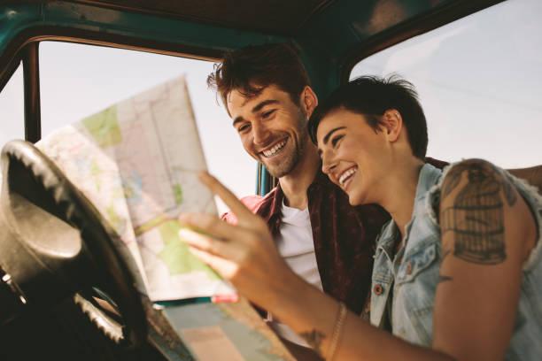 haritaya bakıyordum bir yolculuğa genç gezginler - araba yolculuğu stok fotoğraflar ve resimler