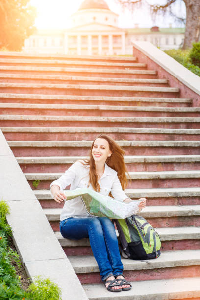 Young travelling woman sitting with map on stairs stock photo