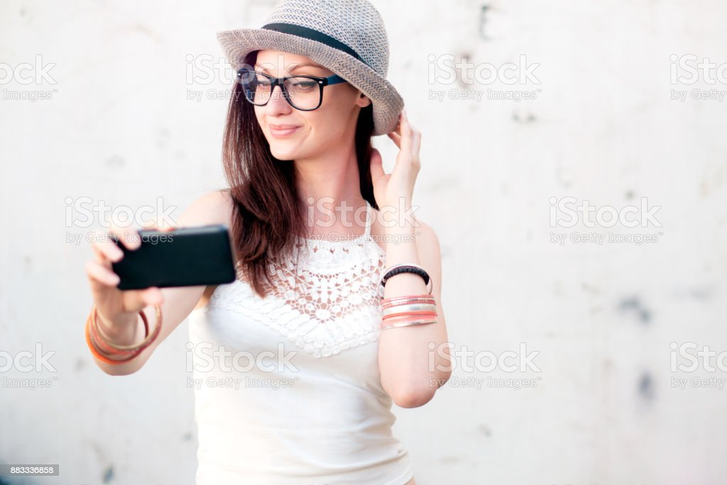Young trendy fashionable girl taking a selfie for instagram stock photo