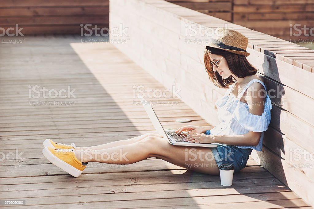 Young trendy girl using a laptop outdoors stock photo