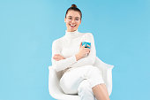 istock Young trendy positive female sitting in armchair, holding tea cup in hands, enjoying her free time from work or studies, isolated on blue background 1252905117
